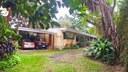 Frente de la casa principal y el estudio, al lado izquierdo un parqueo.