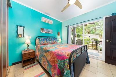Masterbedroom with patio doors overlooking lush gardens